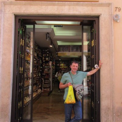 Man, standing in the doorway of a shop, in Rome, Italy.