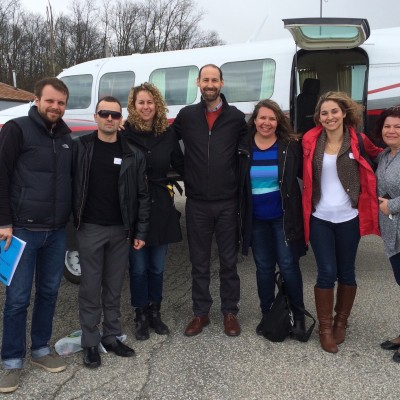 Dr Ian Shulman and a group of five people stand outside an aircraft after taking his flying anxiety treatment program.