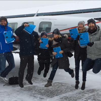 Happy group, jumping beside an airplane.