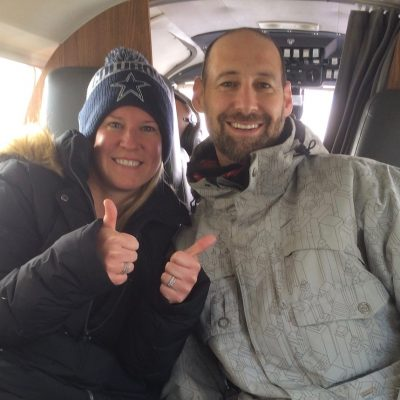 A smiling woman gives a big thumbs up with Dr. Ian Shulman on an airplane flight.