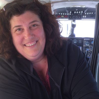 Woman smiling on a small plane after 9 years of being too afraid to fly.