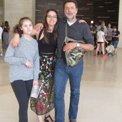 A family standing inside The Louvre, in Paris.