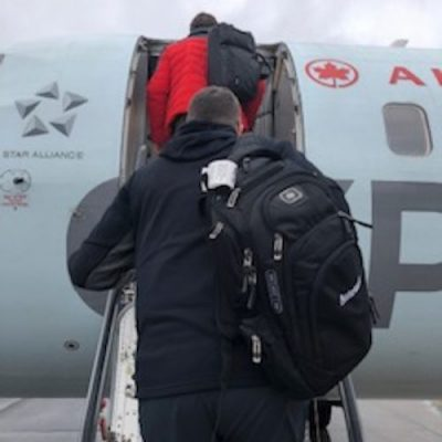 A man wearing a backpack as he climbs the stairs to board an Air Canada flight.