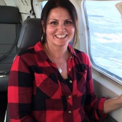 Woman, smiling broadly on a small aircraft.